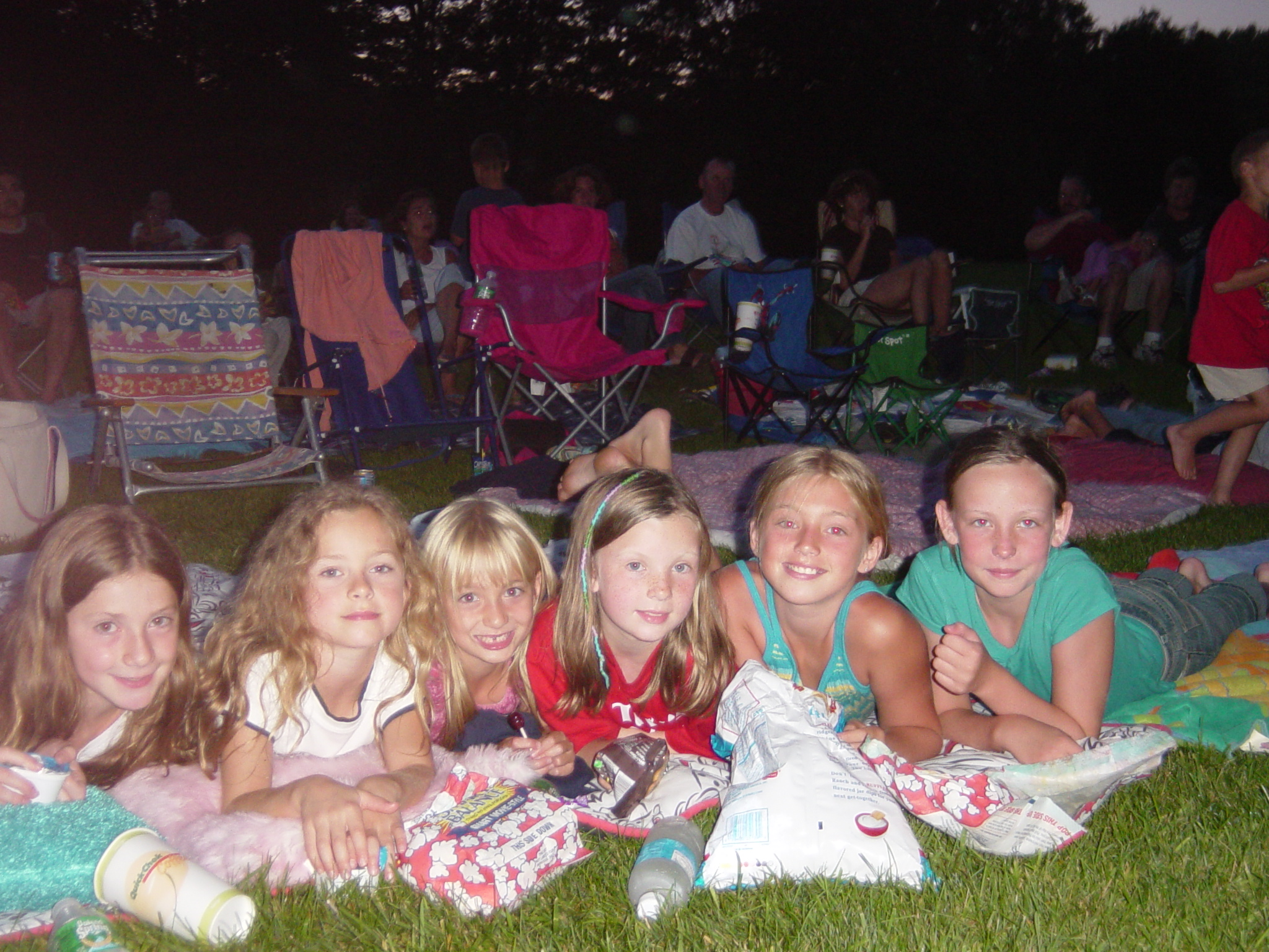 girls lined up lying on a blanket to watch movie